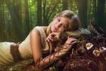 Blond girl dressed in dress walk in a magic forest