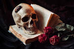 Human skull on book with flowers