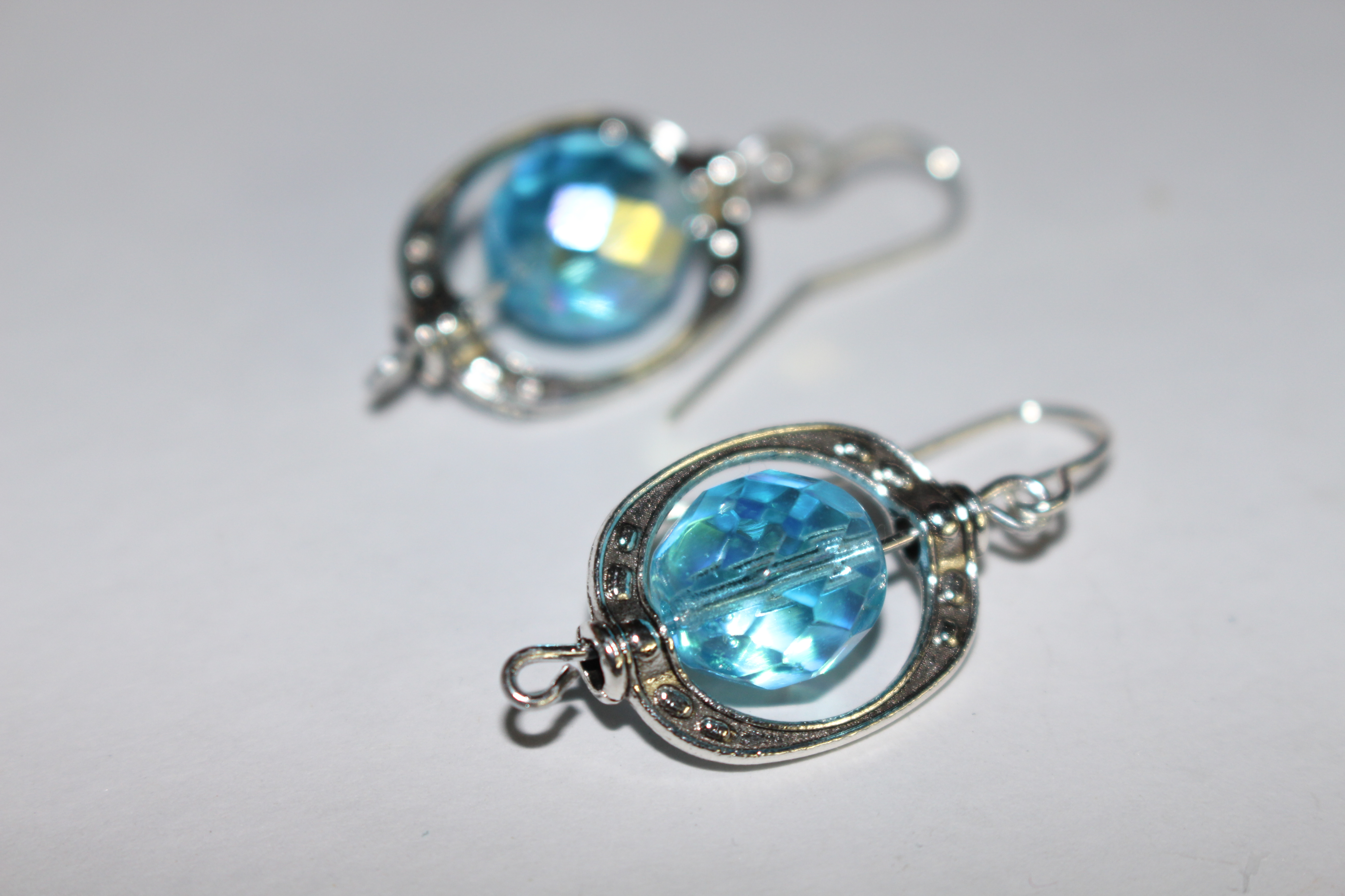 silver earrings with cut blue bead center by