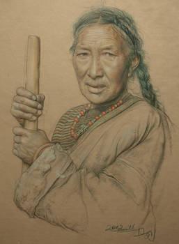 Portrait of Tibetan woman making cheese