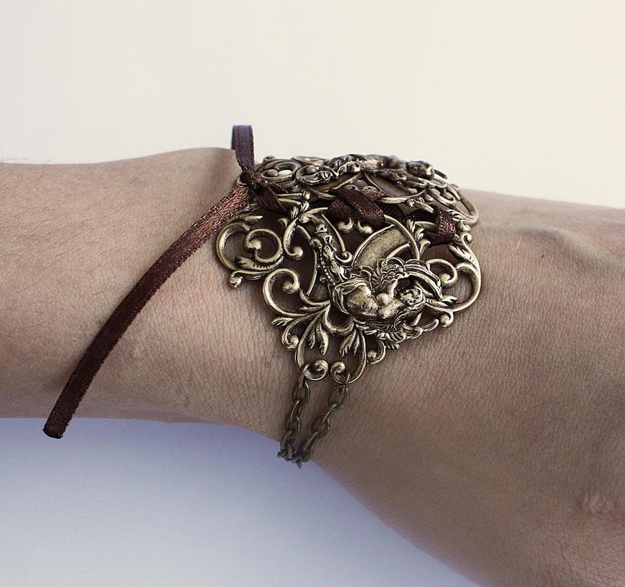 Winged goddesses brass bracelet by Pinkabsinthe