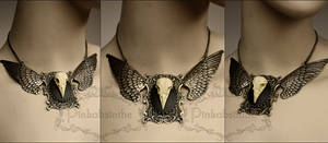 Chest tattoo moth winged skull necklace