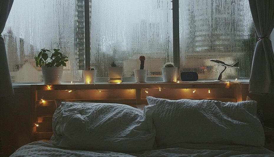 Картинка кровати возле окна с дождем