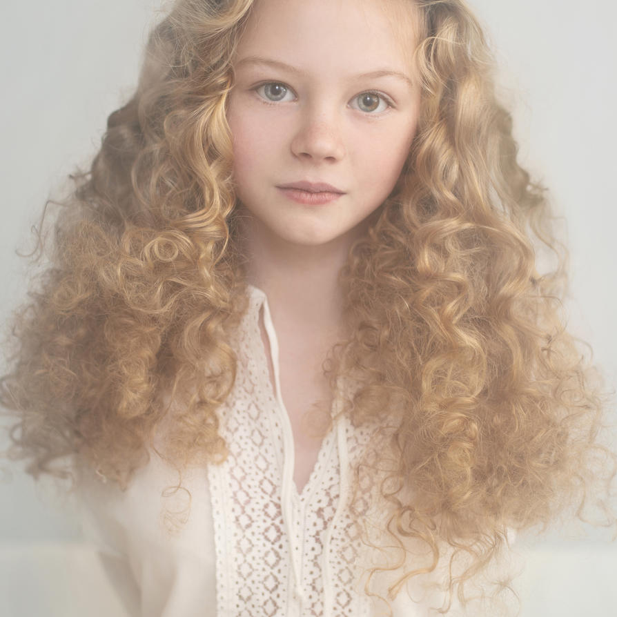 Girl with brown curly hair and blue eyes
