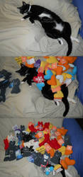 Plushies piled on top of a purring Pickles by Dassi121