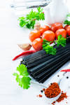 Uncooked black pasta with tomatoes, herbs, spices