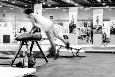 Young man jumping a pommel horse