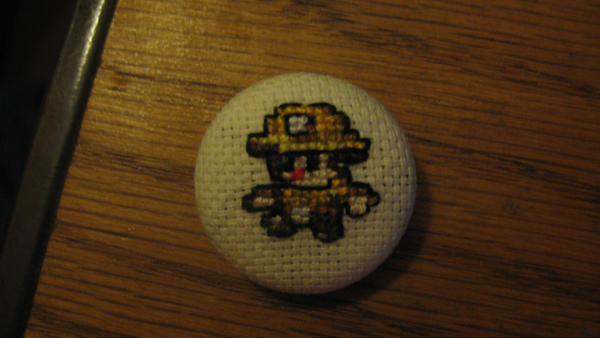 Spelunky cross-stitched button by Romaen