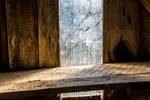 Old wooden shelf in loft in front of window