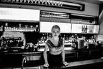Nice barman woman invite guests with smile