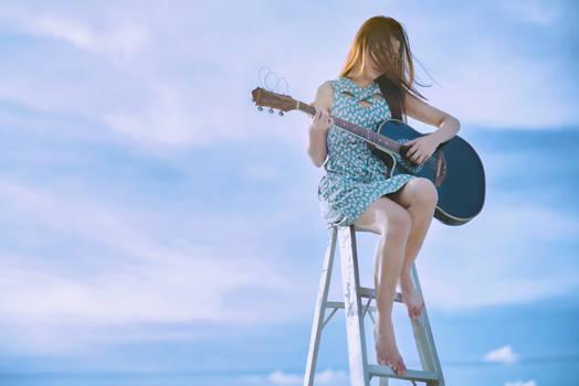 Girl playing guitar on the sky