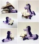 Purple unicorn with books