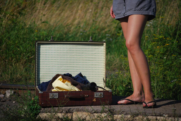 Picture of a suitcase and legs with sandals.