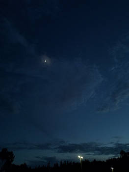 Twilight clouds dance the Moon