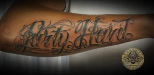 Chicano lettering forearm tat