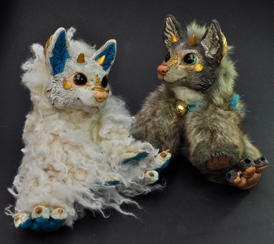 Two resin dragon-foxes by Magweno