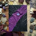Black and purple stitched necronomicon