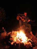 Playing guitar next to the campfire by 92CaptainWolf