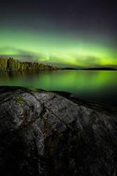 Northern lights glowing over lake