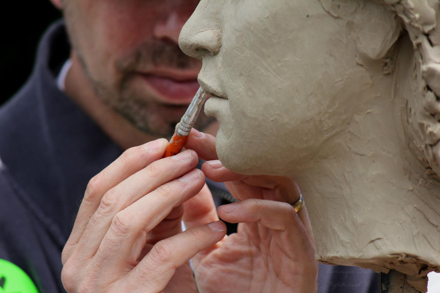 A picture of a man sculpting a clay sculpture of a head.