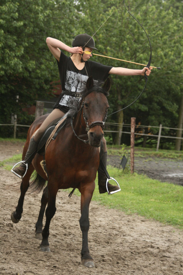 young rider with bow and arrow galloping