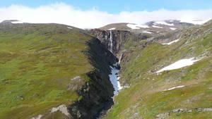 Flying towards a mountain waterfall