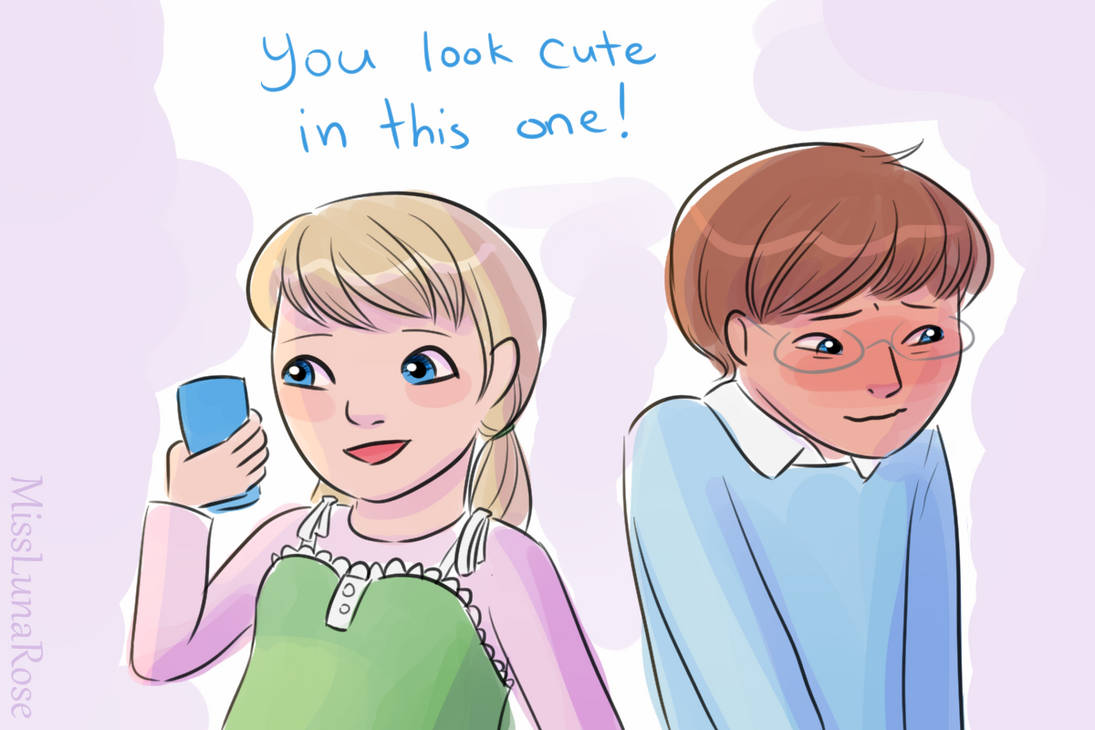 """A girl looks at photos on her phone and says """"You look cute in this one!"""" to a blushing boy."""