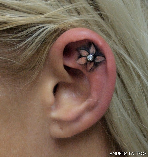 ear tattoo with piercing - flower tattoo