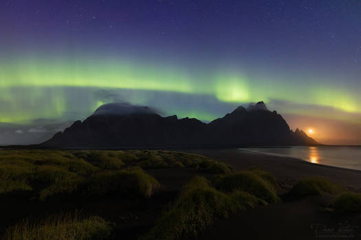 The rising moon under the northern lights
