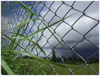view thru chainlink 1 - clouds by nyquiljer