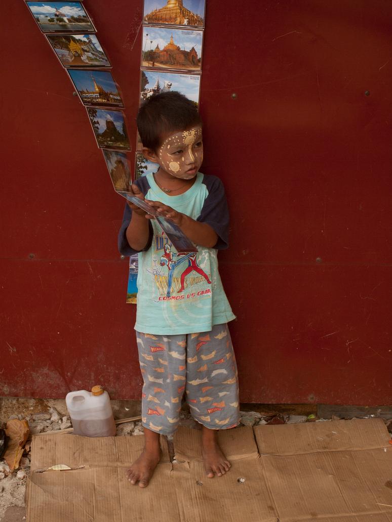 Small Boy Selling Post Cards in Yangon, Myanmar by vanfoto