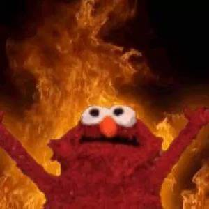 The muppet Elmo raising his hands with a background of fire