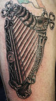 Geiger styled harp tattoo