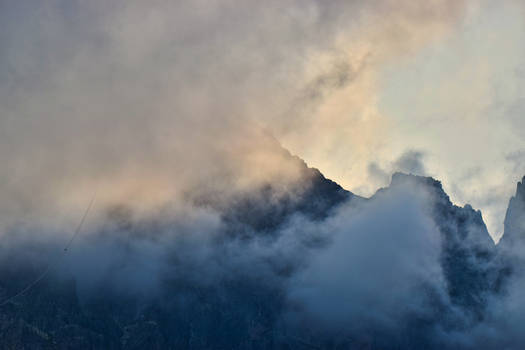 Mountain peaks hiding under evening clouds II
