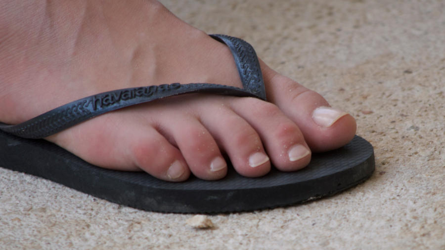 Black women feet in flip flops toenails