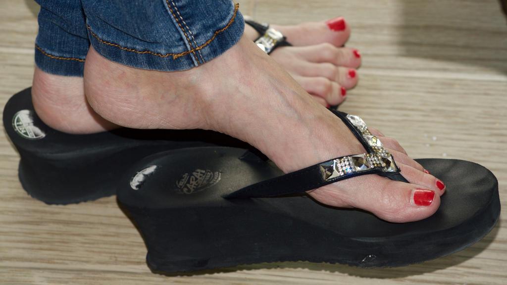 Black women feet in flip flops toenails agree