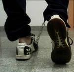 Boy in Umbro indoor sneaks, ankles in legirons. by SneakerBoyBondage