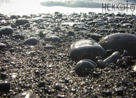 Wet rocks on black beach by Hekkoto