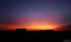 Sunset above city by Saadenika