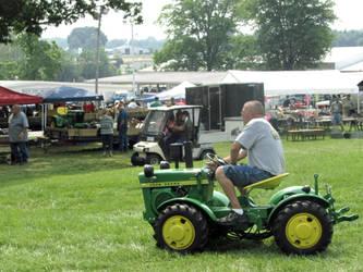 A Man on a Strange Garden Tractor by Artlune
