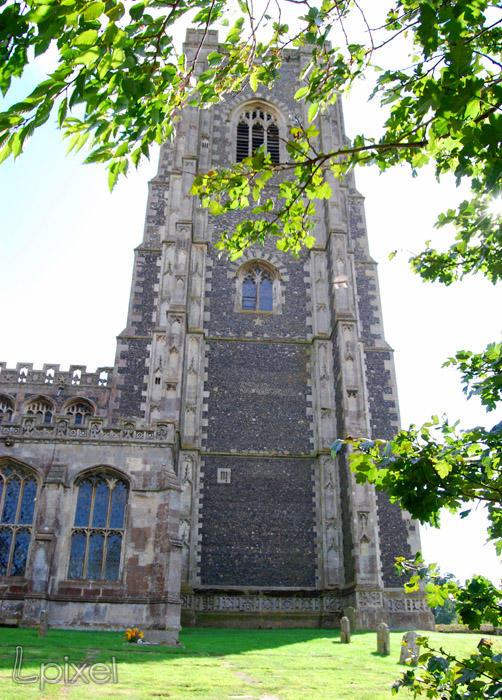 Lavenham church through trees by Lpixel
