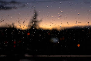 Raindrops on a window with a sunset in background by Hrasulee