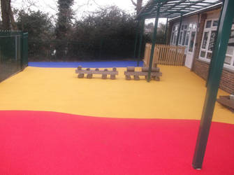 Colourful wetpour play area flooring installation by PlaygroundMarkings