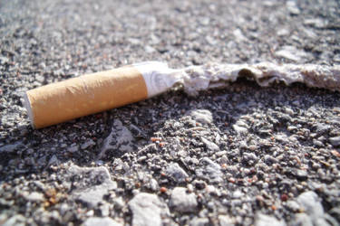 Cigarette on the road by Tamyte